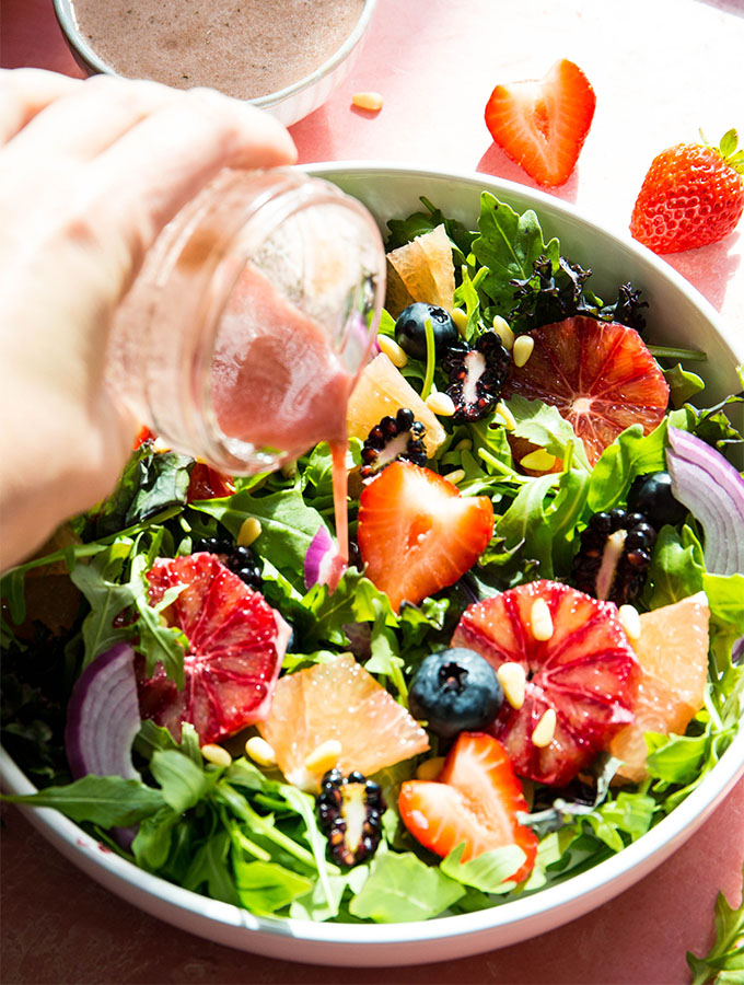 A hand is pouring the pomegranate salad dressing onto the salad.