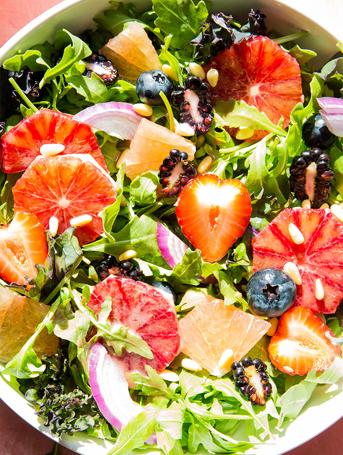 Winter salad contains kale, arugula, berries, citrus, and pine nuts.
