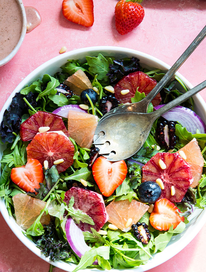 The winter salad is plated in a white bowl next to a bowl of salad dressing and strawberries.