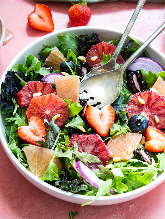 Winter salad is plated in a white bowl with antique fork and spoon.
