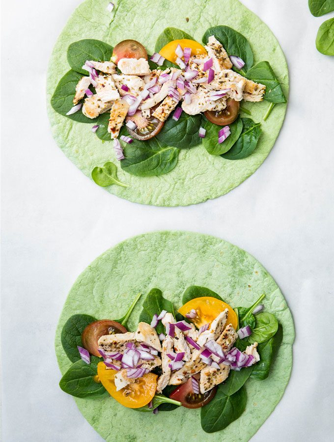 Chicken wraps are plated on parchment paper and are assembled.