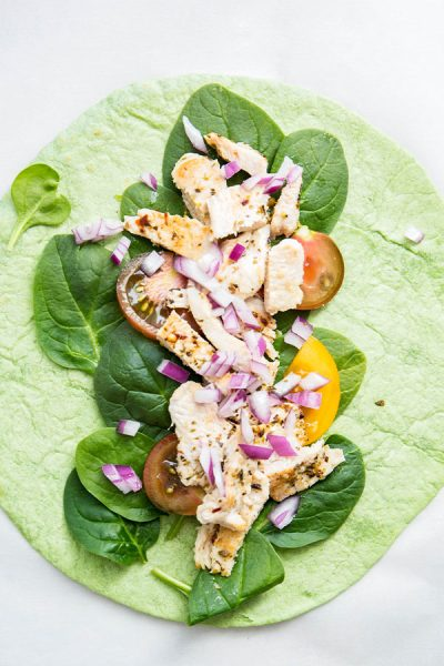 Italian chicken wrap is topped with chicken, spinach, red onion, and tomato.