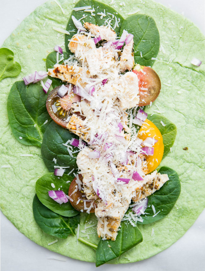 Parmesan cheese is sprinkled on top of the chicken wraps before it is folded.