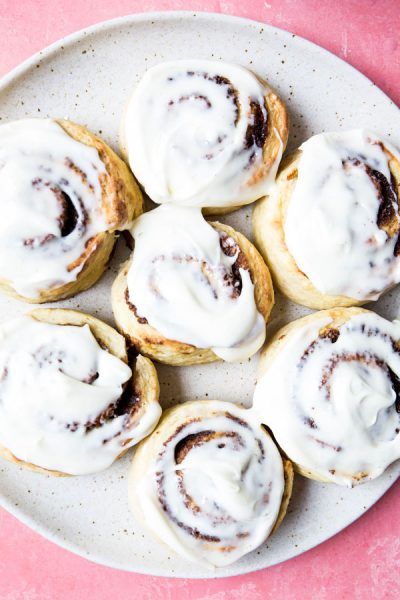 Cinnamon rolls are frosted with cream cheese frosting.