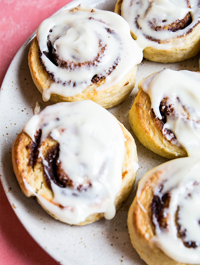 Cinnamon rolls are topped with cream cheese frosting on a speckled plate.