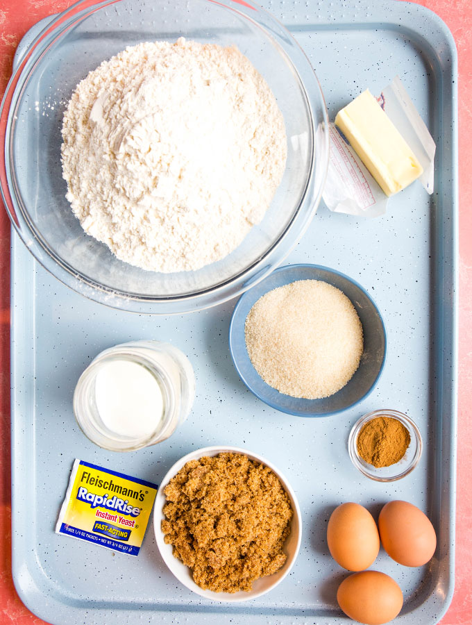 Cinnamon roll ingredients are displayed individually on a blue baking sheet.