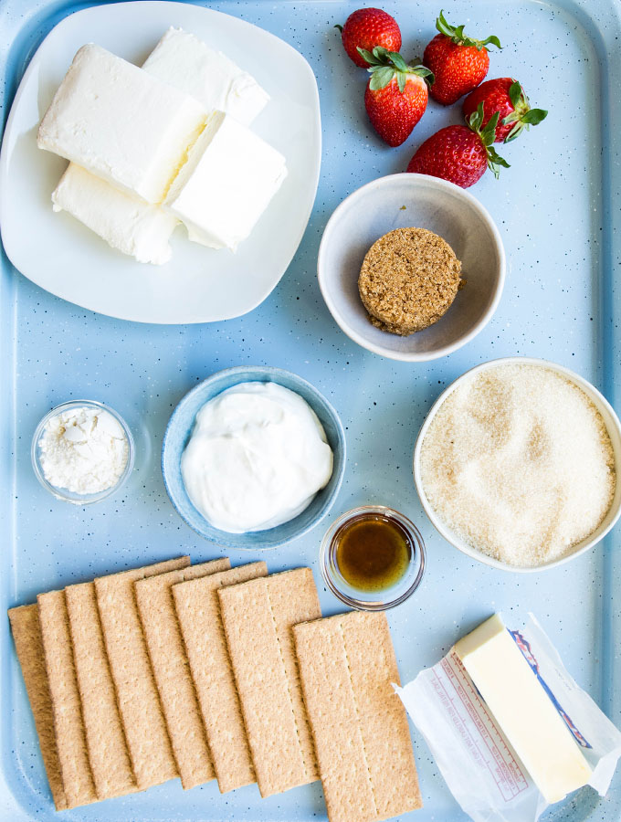 Strawberries and cream cheesecake ingredients are displayed individually on a blue baking sheet.