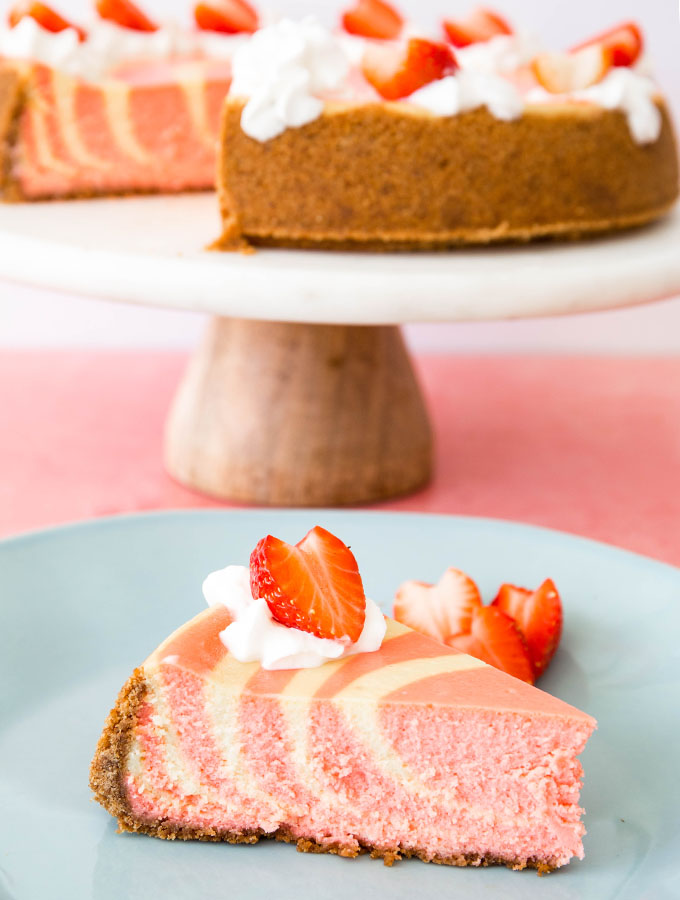 A slice of strawberries and cream cheesecake is plated on a blue plate.
