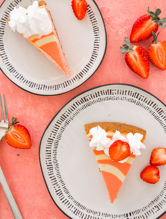 Slices of cheesecake are plated on plated next to sliced strawberries.
