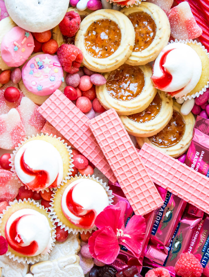 Treats like wafers, cupcakes, cookies, fruits, and candies are placed on the board.