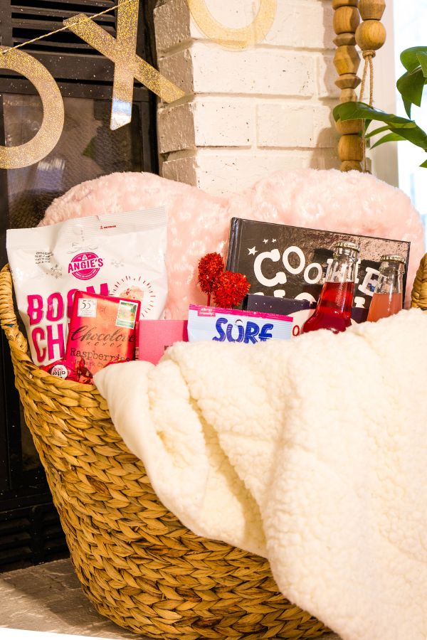 Valentine's Day gift basket is assembled in a wicker basket and includes candy, a blanket, and books.