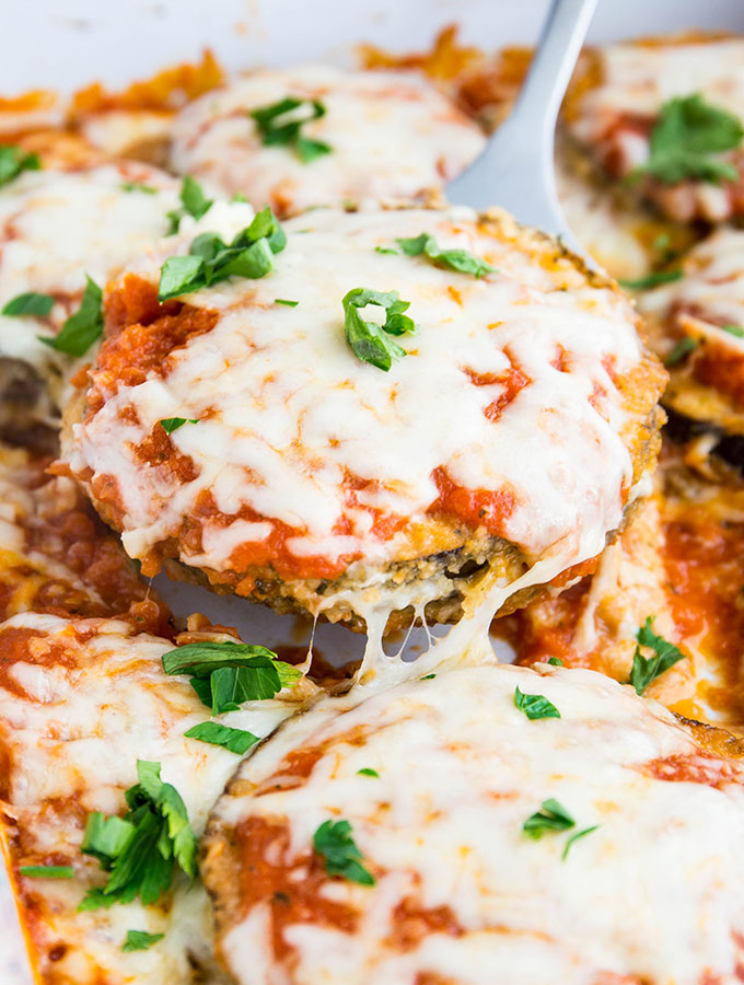 A spatula is lifting slices of eggplant parmesan out of the baking dish.