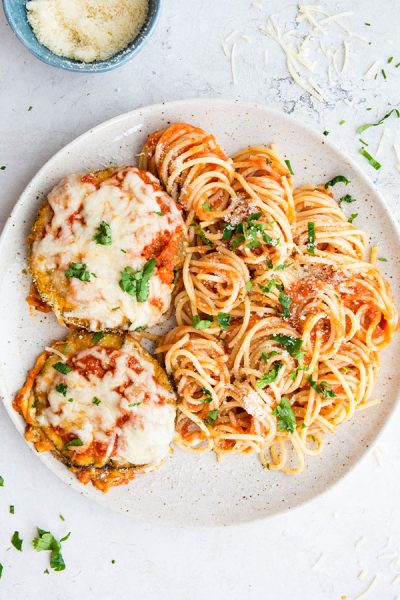 Eggplant parmesan and spaghetti is plated on a plate and topped with cheese and parsley.