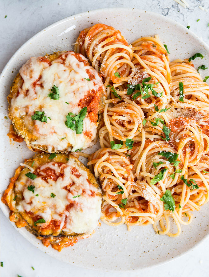 Eggplant parmesan and spaghetti pasta is plated on a speckled plate and topped with parsley.