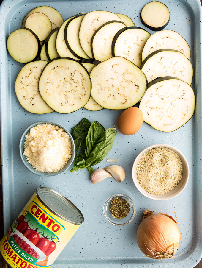 Eggplant parmesan ingredients are displayed individually on a blue baking sheet.
