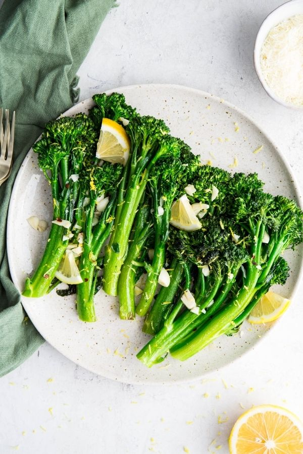 Broccolini is plated on a speckled plate and topped with lemon wedges.