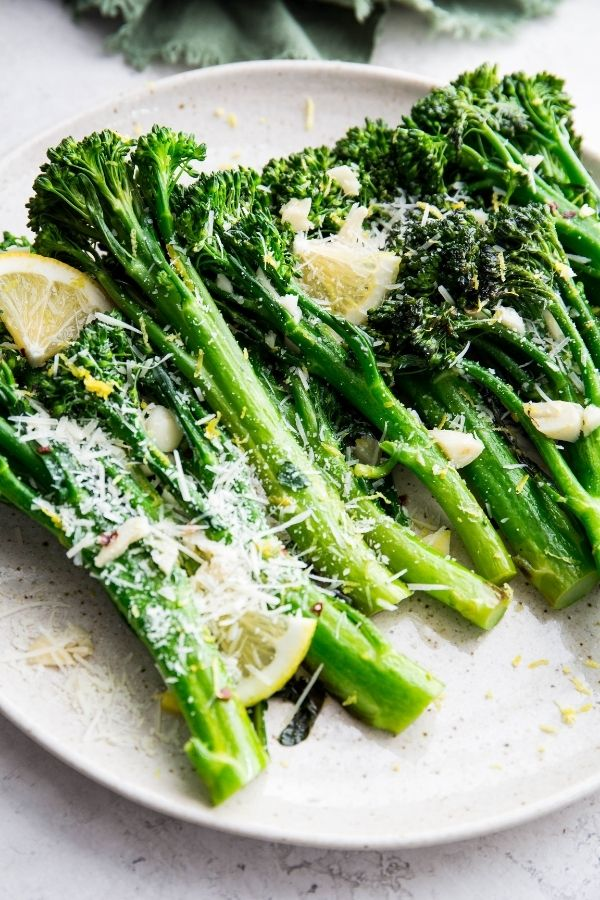 Parmesan is sprinkled on top of the broccolini and lemon wedges.