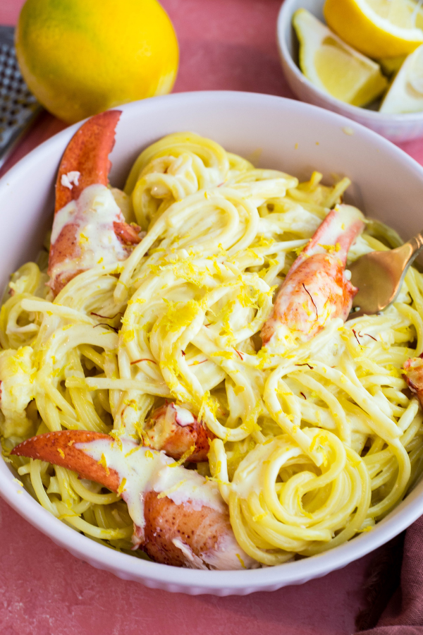 Lemon zest is sprinkled over the pasta in a white bowl.