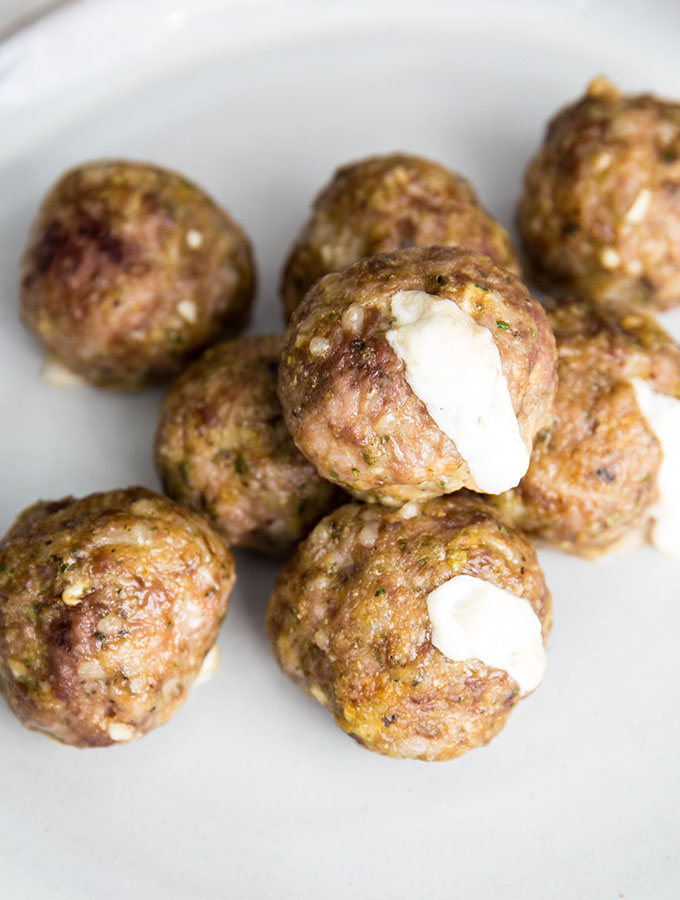 Cheese is oozing out of the meatballs after they are baked.