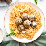 Mozzarella stuffed meatballs are plated in a bowl next to a napkin and fresh basil.