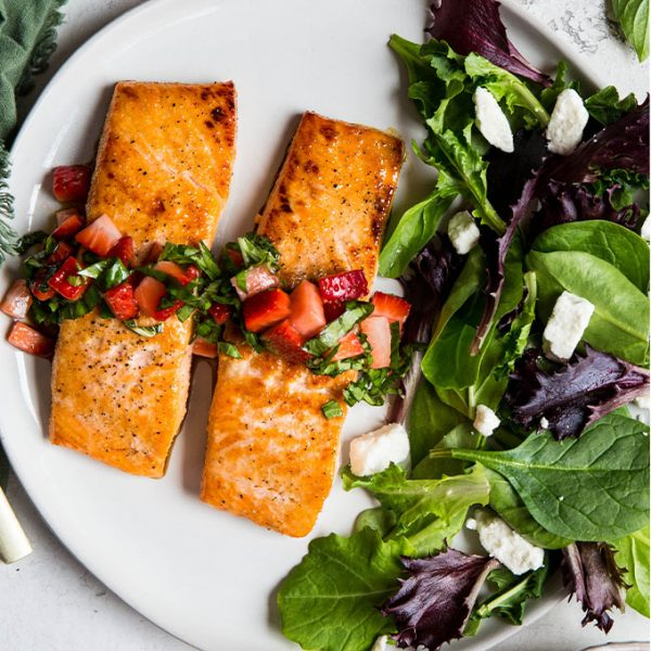 Salmon fillets are plated next to a salad and topped with fresh strawberry and basil relish.