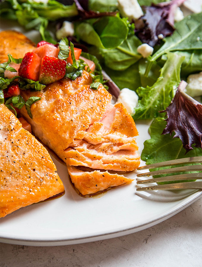 Salmon is flaked with a fork to show the juicy, tender texture.