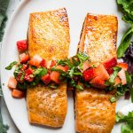 Salmon fillets are topped with fresh strawberry relish and plated next to a salad.
