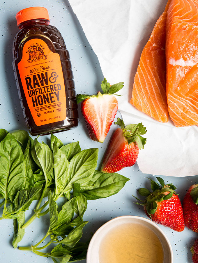 Balsamic glazed salmon ingredients are displayed individually and includes salmon, honey, vinegar, strawberries, and basil.