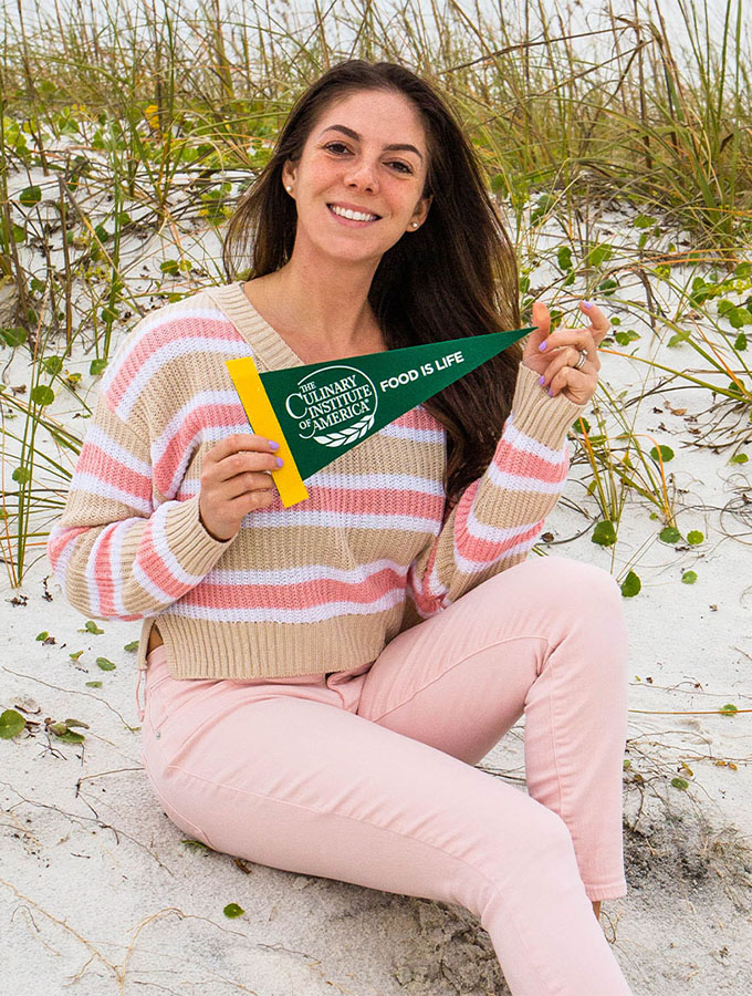 Sherry is holding a CUlinary Institute of America flag while sitting in a sand dune.