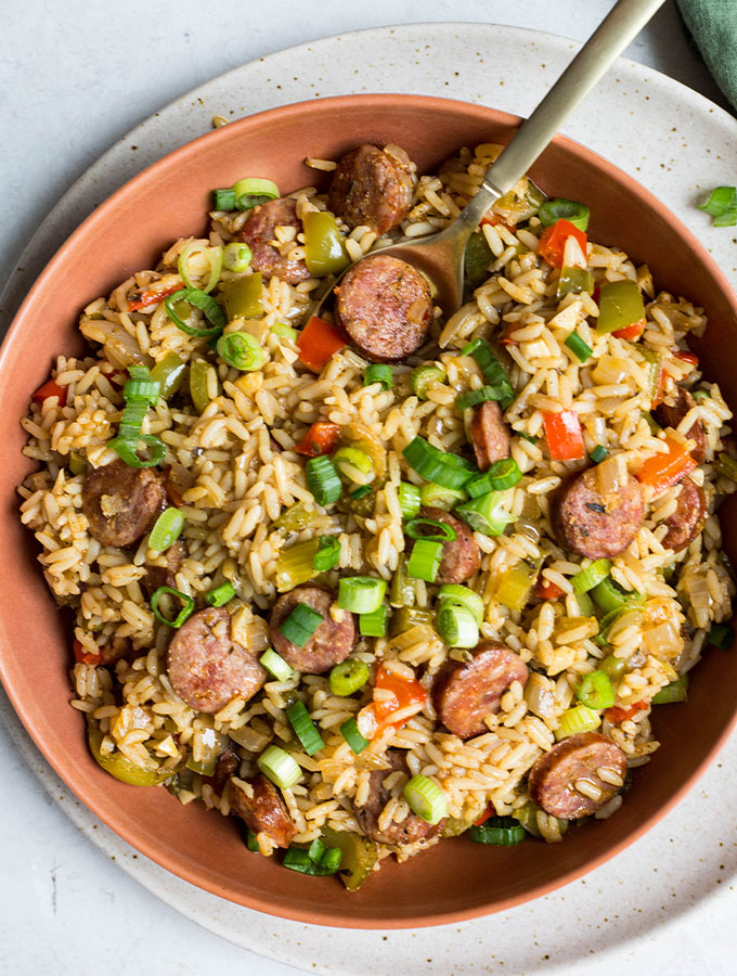 Cajun rice is plated in a red bowl and stirred with a gold spoon and topped with green onions.