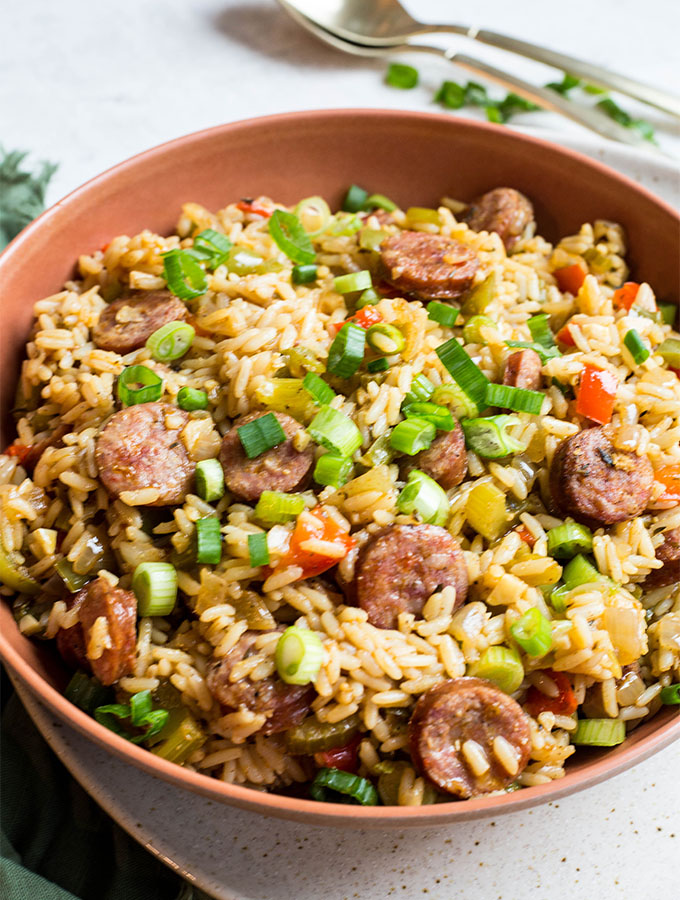 Cajun dirty rice is plated in a red bowl and topped with green onions.