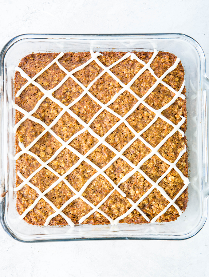 Carrot cake breakfast bars are baked in a 9X9 glass baking dish and topped with icing.