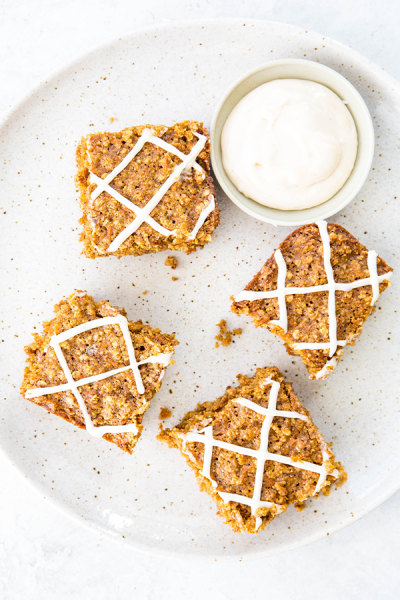 Carrot cake oatmeal bars are sliced and plated on a plate next to a bowl of the icing.