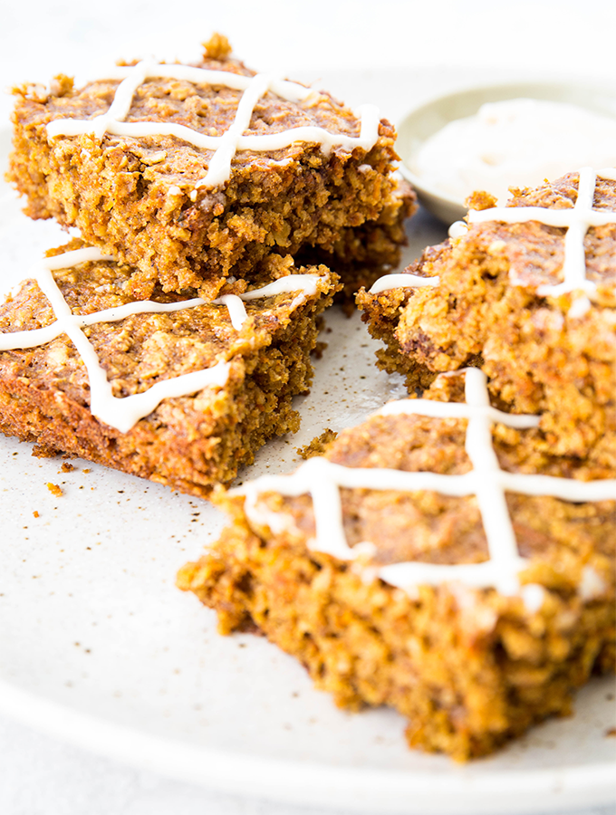 Carrot cake oatmeal bars are sliced and stacked on a beige plate.