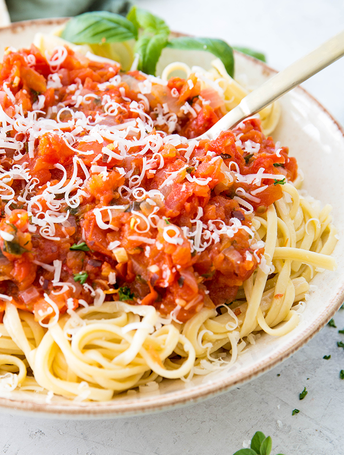 A closeup shot shows the chunky texture of the sauce that is placed over the spaghetti.