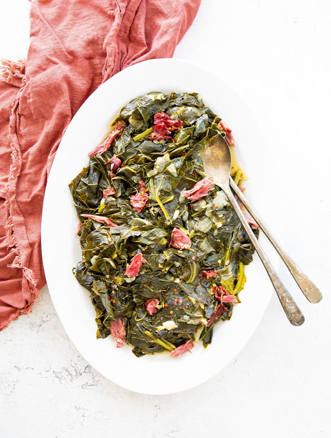 Collard greens and smoked turkey necks are plated on a white plate with two utensils.