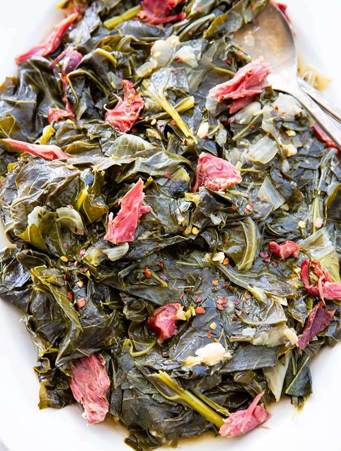 Collard greens are plated and topped with shredded smoked turkey and red pepper flakes.