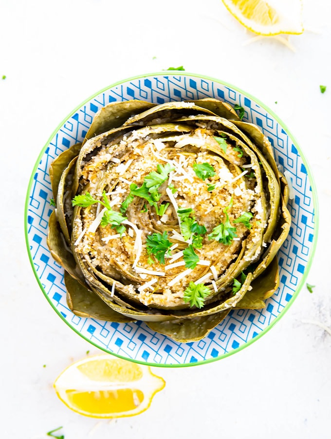 The artichoke is stupped, simmered on the stove top, then topped with fresh parsley, cheese, and wedges of lemon.