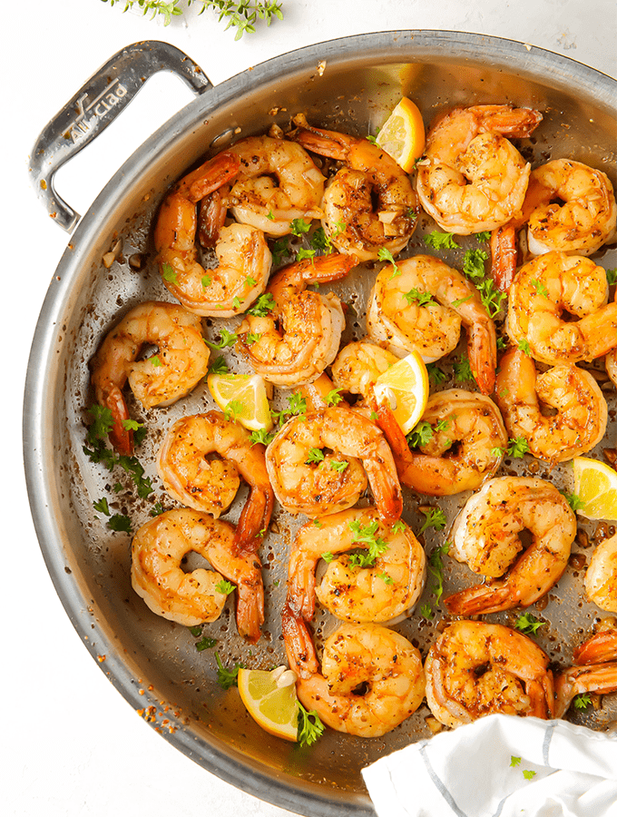 Shrimp is cooked in one pan and topped with lemons and parsley for added flavor.