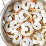 Shrimp is placed in a pan to sear them quickly with butter and spices.