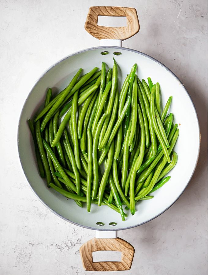 Green beans are sauteed in a large white pan on the stovetop.