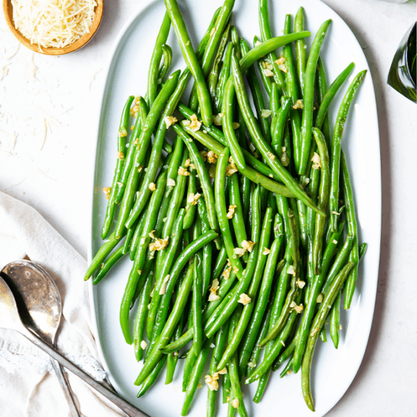 Green beans are plated on a white platter next to a small pinch bowl full of parmesan cheese.