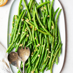 Green beans are plated on a white serving platter and topped with crispy garlic bits.