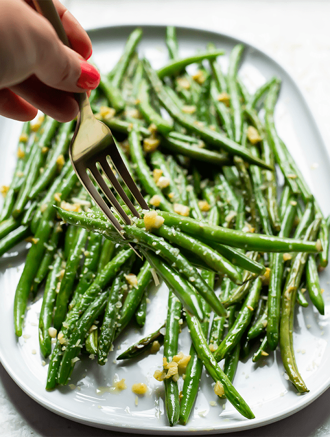 A fork is piercing tender green beans that are topped with parmesan cheese.