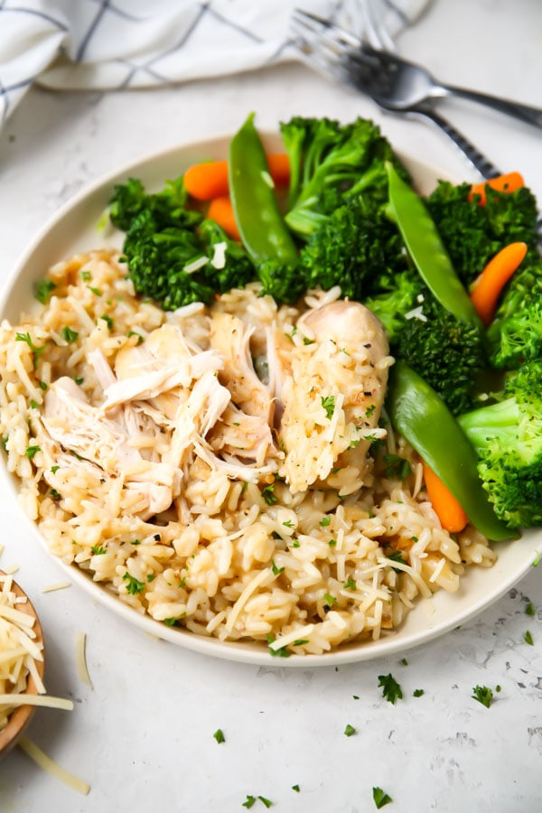 A chicken thigh is shredded on top of a bed of rice.