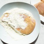 Chicken is seasoned with garlic, salt, and pepper, then dredged in flour.