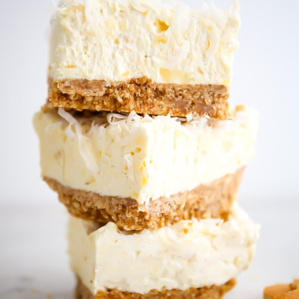 Cheesecake bars are stacked next to vanilla wafers.