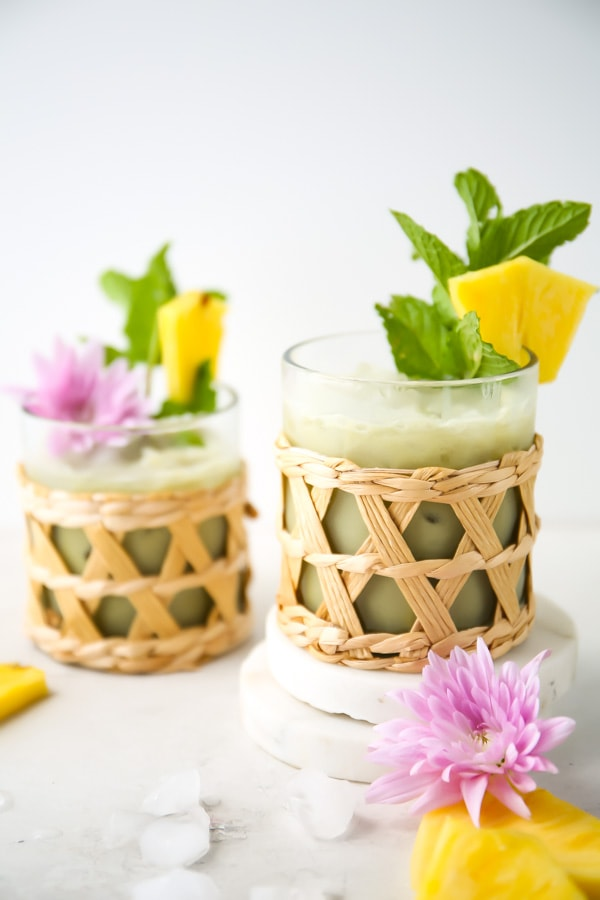 Pineapple matcha drink is poured into two separate glasses and plated next to flowers and pineapple slices.