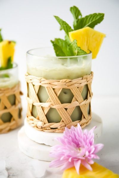 Pineapple matcha drink is poured into a small glass and garnished with mint and fresh pineapple.