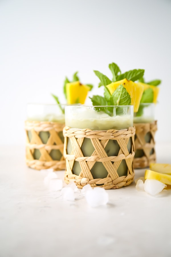 Pineapple matcha drink is poured into three glasses and topped with crushed ice and mint.